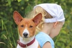 Mädchen und Hund sitzen mit ihren Rückseiten miteinander Lizenzfreies Stockbild