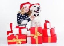 Mädchen und Hund sitzen mit Weihnachtsgeschenken Stockbilder