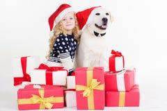 Mädchen und Hund sitzen mit Weihnachtsgeschenken Lizenzfreie Stockfotografie