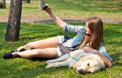 Mädchen und ihr Hund-selfie Sommer auf einem Hintergrund des grünen Grases Lizenzfreie Stockbilder