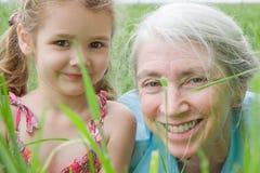 Mädchen und ihre Großmutter im langen Gras Stockfotografie