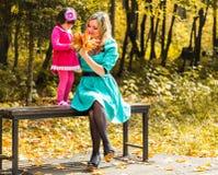 Mädchen und ihre Mutter, die draußen mit herbstlichen Ahornblättern spielen Baby, das goldene Blätter auswählt stockbild