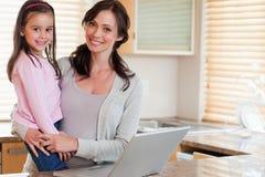 Mädchen und ihre Mutter, die ein Notizbuch verwendet Stockbilder