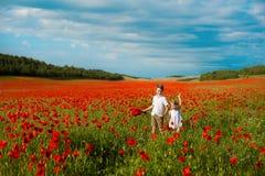 Mädchen und Junge auf einem Gebiet von roten Mohnblumen Konzept der Kindheit, Glück, Familie lizenzfreie stockbilder