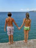 Mädchen und Junge betriebsbereit zum Sprung im adriatischen Meer Stockfotografie