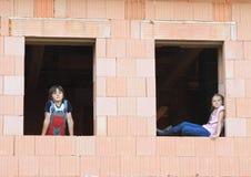 Mädchen und Junge in den Fenstern Stockbild