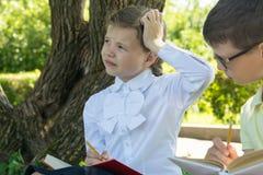 Mädchen und Junge denken an das Lösen einer Aufgabe im Park lizenzfreies stockfoto