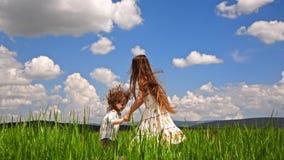 Mädchen und Junge, die auf dem grünen Gebiet springen stock video footage