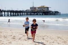 Mädchen und Junge, die auf dem Strand spielen Lizenzfreie Stockfotos