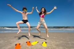 Mädchen und Junge, die auf Strand springen Stockbild