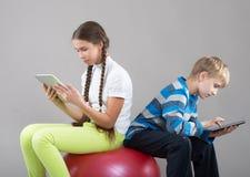 Mädchen und Junge, die Auflagen-Tablet-PC-Schirme betrachten Stockfotos