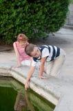 Mädchen und Junge, die durch den Brunnen spielen Stockfotos