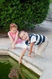 Mädchen und Junge, die durch den Brunnen spielen Stockfotografie