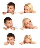 Mädchen und Junge, die hinter einer Anschlagtafel sich verstecken Stockfoto
