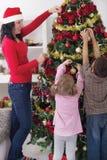 Mädchen und Junge, die ihrer Mutter verziert den Weihnachtsbaum hilft Lizenzfreies Stockfoto