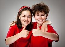 Mädchen und Junge, die okayzeichen zeigen stockfotografie