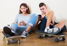 Mädchen und Junge, die online Spiele spielen Lizenzfreie Stockfotografie