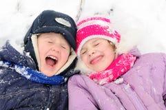 Mädchen und Junge, die am schneebedeckten Winter lachen Stockfotos