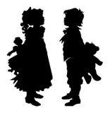 Mädchen und Junge, die schwarzes Schattenbild Teddy Bears und der Puppe halten Stockfotos