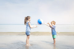 Mädchen und Junge, die Wasserball auf dem Strand spielen Lizenzfreies Stockbild