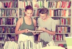 Mädchen und Junge im Buchladen Stockbild