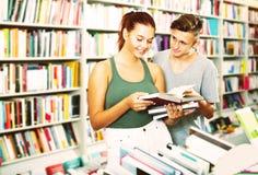 Mädchen und Junge im Buchladen Stockbilder
