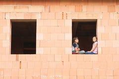 Mädchen und Junge im Fenster Stockfoto