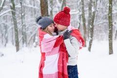 Mädchen und Junge machen warm im Winterwald Lizenzfreie Stockfotos