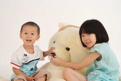 Mädchen und Junge mit Bärenspielzeug lizenzfreie stockfotografie