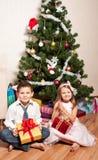 Mädchen und Junge nahe einem Tannenbaum Stockfotos