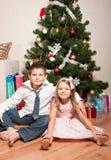 Mädchen und Junge nahe einem Tannenbaum Lizenzfreies Stockbild