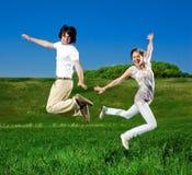 Mädchen und Junge springen Stockfotografie