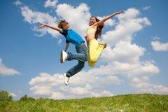 Mädchen und Junge - springend unter Himmel lizenzfreie stockfotos