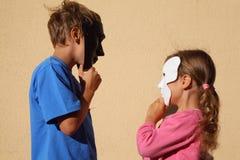 Mädchen und Junge tragen Schablonen und betrachten einander Stockfoto