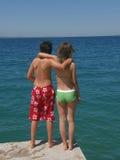 Mädchen und Junge umfaßt auf Strand Lizenzfreie Stockfotos