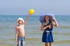 Mädchen und Junge zeigen, dass zu nehmen ist notwendig, von der Sonne auf dem Meer Stockfoto