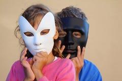 Mädchen- und Jungenfellgesichter hinter Schablonen Stockfotos