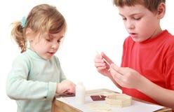Mädchen- und Jungenfertigkeiten am kleinen Tisch Stockfotografie