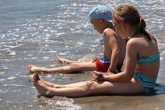 Mädchen- und Jungenlagerung auf dem Strand. Stockfotografie