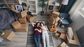 Mädchen und Kerl, die das Lügen auf Boden nachdem dem Bewegen auf neue Wohnung plaudern und gestikulieren stock video