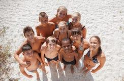 Mädchen und Kerle auf Sand auf Sommerferien lizenzfreies stockfoto