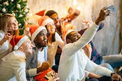 Mädchen und Kerle in Sankt-Hüten, die selfie an der Partei tun Weihnachten, Konzept des neuen Jahres lizenzfreie stockfotos