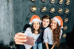 Mädchen und Kerle in Sankt-Hüten, die selfie an der Partei tun Weihnachten, Konzept des neuen Jahres stockfotografie