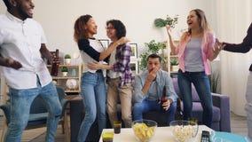 Mädchen und Kerle sind glücklich, nachdem sie im Fernsehen Sportspiel zu Hause zusammen aufgepasst haben stock video footage