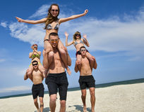 Mädchen und Kerle am Strand Stockbild