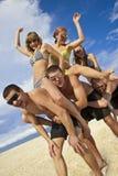 Mädchen und Kerle am Strand Lizenzfreie Stockbilder