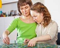 Mädchen und Mamma, die Puzzlespiel tun Stockfotos