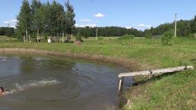 Mädchen und Mann mit Hut springen in Teich vom Steg Spaß im Freien stock footage