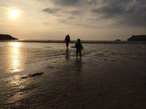 Mädchen und Mutter, die auf Sonnenuntergangstrand gehen lizenzfreie stockfotos