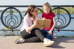 Mädchen und Mutter, die das Buch lesen lizenzfreie stockbilder